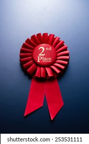 Red second place winner of the socket with a pleated ribbon on a dark background