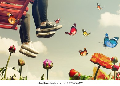 Red seesaw swinging in the air space flying high with butterflies over colorful flowers. Feet of girls in sports shoes over the edge in the blue sky. Childhood fantasy world. Minimalist surreal image
