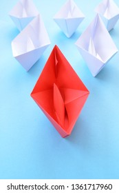 A red self-folded paper boat lies on a blue surface, followed by many white boats - concept symbolizing leadership