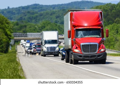 A red semi leads a line of traffic down an interstate highway in Tennessee.  Heat rising from the pavement gives background trucks and forest a cool shimmering effect.