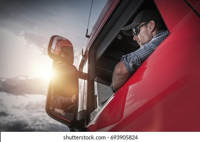 Red Semi Truck. Caucasian Truck Driver Preparing For the Next Destination.
