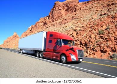 Red semi truck driving through Southwest, Arizona-USA