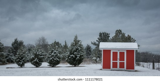 A red shed beneath a heavy winter sky after a light snowfall