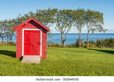 Red shed with blue sky and green grass in Gaspe Peninsula, Quebec, Canada