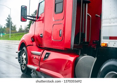 Red shiny big rig popular professional reliable bonnet long haul semi truck transporting commercial cargo in dry van semi trailer moving on the straight wide wet highway road in rainy weather