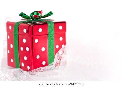 Red shiny polka dot Christmas present on shimmery fabric