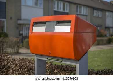 A red shiny and public postbox in a residential area in the Netherlands