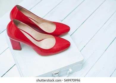 Red shiny shoes with high heels isolated on a white wooden background.