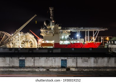 RED SHIP WITH A HELIPAD - Pipe laying vessel moored in seaport