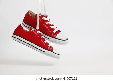 Red Shoe / Sneakers hanging with soft shadow - isolated on white. Plenty of copy space.