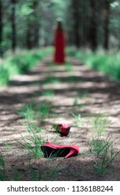 Red shoes fallen on forest path with blurred woman in background.