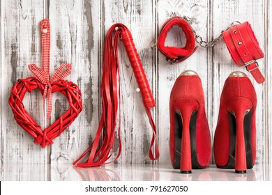 red shoes lash heart handcuffs on a wooden background