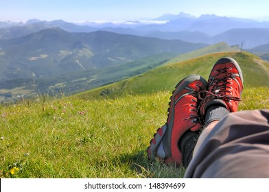 red shoes walking an lying hiker  front of a mountainous landscape