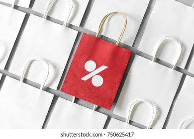 Red shopping bag from recycle paper with percent sign in a row of white shopping bags on gray background. Black friday or Christmas sales.