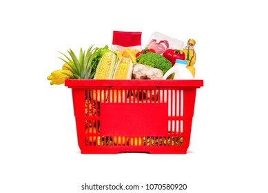 Red shopping basket full of food and groceries, studio shot isolated on white background