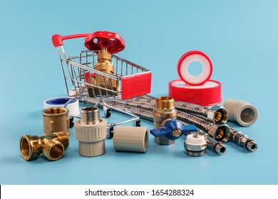 red shopping cart with brass gate valve closeup. ball valve, coupling, corner, sealing tape, flexible hoses and polypropylene fittings on blue background. pipeline installation, shopping concept.