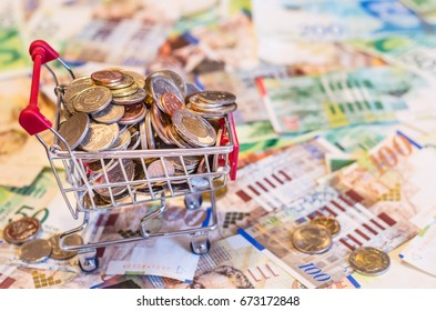 red shopping cart full of coins stands on banknotes background