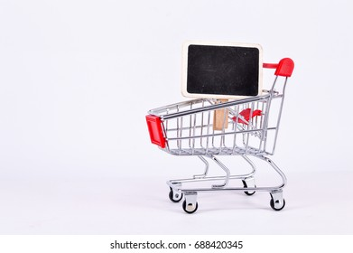 Red shopping cart isolated on white background with blackboard for your text. Selective focus.