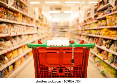 red shopping cart in supermarket aisle