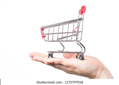 Red shopping cart trolley on hand isolated on white background. Side view. Shopping concept.