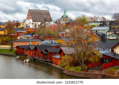 Red shore houses on the riverbank of Porvoo river. Old town of Porvoo in Finland in autumn.