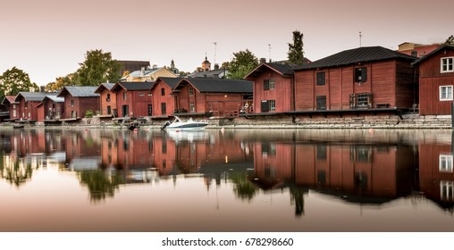 Red shore houses on the riverbank of Porvoo river. Porvoo, Finland. Old town of Porvoo in Finland late afternoon.