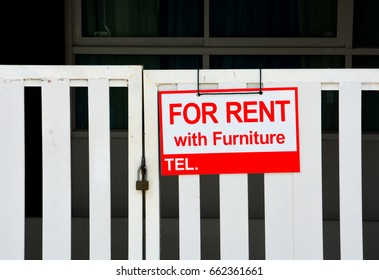 red sign with the inscription house for rent with furniture hanging on closed white fence, copy space