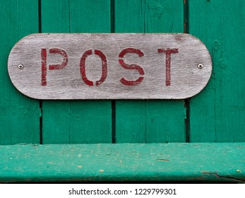Red sign of an old vintage mail letter box post on green wood with space for text and graphics