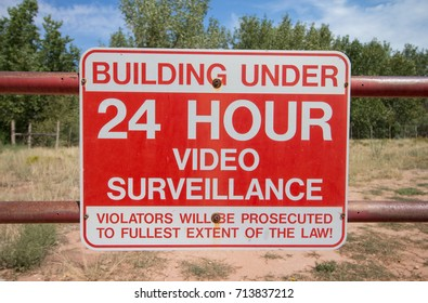 "A red sign on a gate reads, ""Building Under 24 Hour Video Surveillance. Violators will be prosecuted to the furthest extent of the law""."