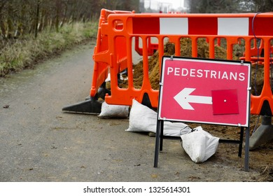 A red sign for pedestrians next to some road works
