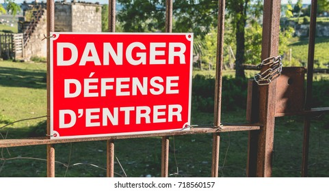 red sign placed on a rusty gate or it is written in French - danger defended to enter