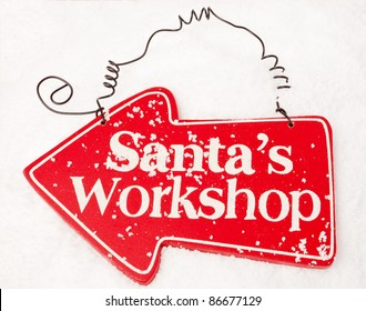 A red sign showing the way to santas workshop sat in snow