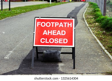A red sign stating footpath closed