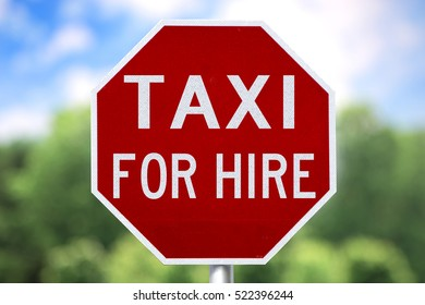 Red Sign - Taxi For Hire. Blue Sky.  Green trees.  White Clouds