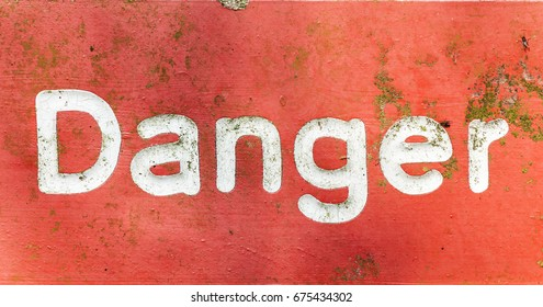 Red signage with the word danger painted in white letters. An old metal sign covered in green algae scratches flies and rust