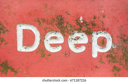 Red signage with the word deep painted in white letters. An old metal sign covered in green algae scratches and rust