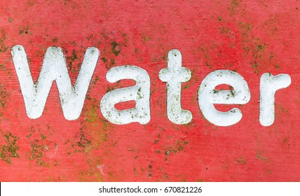 Red signage with the word water painted in white letters. An old metal sign covered in green algae scratches and rust