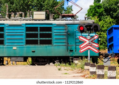 Red signal of semaphore and stop sign in front of railroad crossing with train passing
