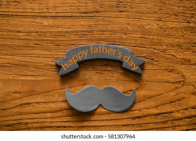 red signboard with black paper mustache, happy fathers day in italian, against a brown wooden table background. Empty space for inscription.