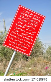 Red signboard warning about entrance to palestinian settlement. Central Israel.