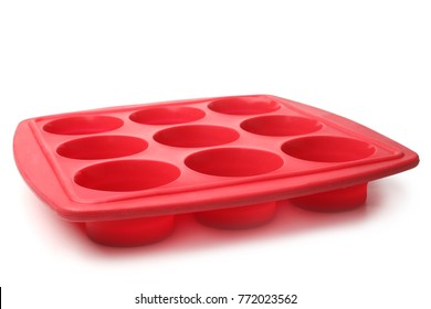 Red silicone form for cooking muffin and cupcake on white background