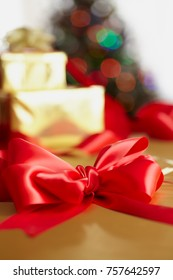 A red silk bow in the foreground with stacked Christmas presents, tree and lights, in the background.