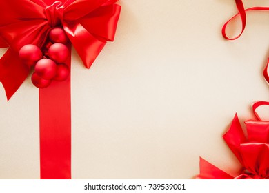 Red silk bow and ribbon on satin background with Christmas balls and room for copy space.