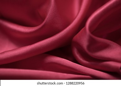 Red silk fabric material for lingerie folded randomly, creating unique background textures variations.