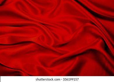 Red silk fabric texture with soft folds - beautiful background.