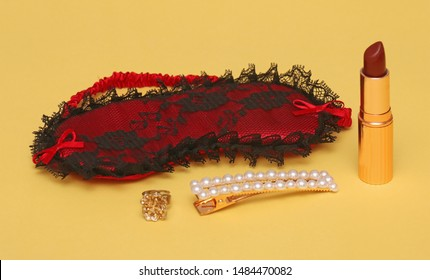 Red silk face sleep mask with lipstick and hair pin on yellow background