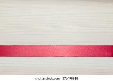 The red silk ribbon or red silk strip  on the wooden texture background.