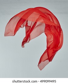 red silk in wind on grey background