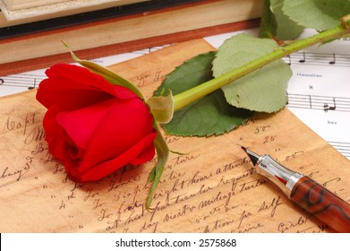 red silky rose with vintage pen and letter