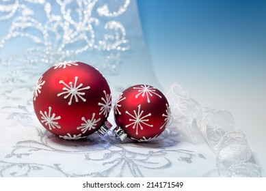 Red and silver Christmas decorations on blue background, text space. Shallow DOF, focus on the knot